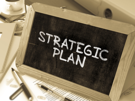 strategic plan: Strategic Plan Handwritten by white Chalk on a Blackboard. Composition with Small Chalkboard on Background of Working Table with Office Folders, Stationery, Reports. Blurred, Toned Image. 3D Render.