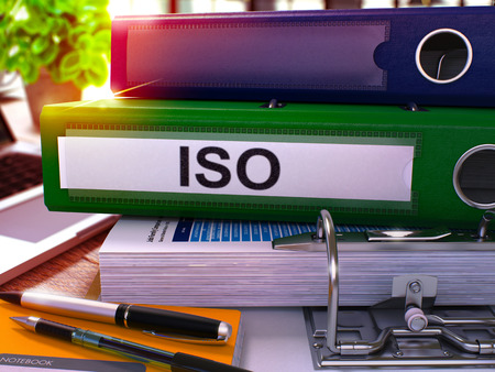 standardization: Green Ring Binder with Inscription ISO - International Organization Standardization - on Blurred Background of Working Table with Office Supplies and Laptop. ISO - Toned Illustration. 3D Render.