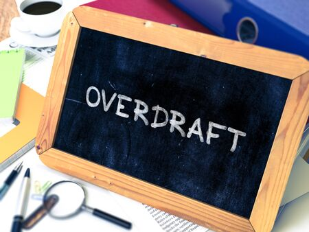 overdraft: Overdraft - Chalkboard with Hand Drawn Text, Stack of Office Folders, Stationery, Reports on Blurred Background. Toned Image. 3D Render. Stock Photo