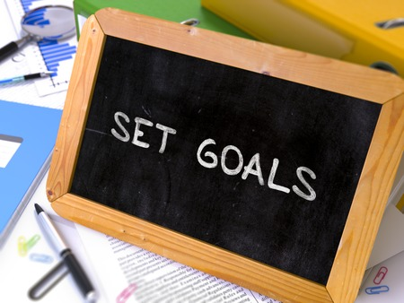 ring binders: Set Goals Handwritten on Chalkboard. Composition with Small Chalkboard on Background of Working Table with Ring Binders, Office Supplies, Reports. Blurred Background. Toned Image. 3D Render.