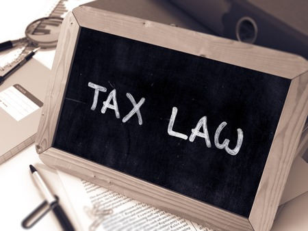 tax law: Tax Law Concept Hand Drawn on Chalkboard on Working Table Background. Blurred Background. Toned Image. 3D Render.