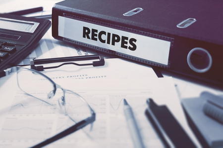 prescript: Recipes - Office Folder on Background of Working Table with Stationery, Glasses, Reports. Business Concept on Blurred Background. Toned Image. Stock Photo