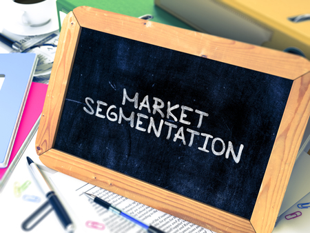 stationery needs: Market Segmentation Handwritten by White Chalk on a Blackboard. Composition with Small Chalkboard on Background of Working Table with Office Folders, Stationery, Reports. Blurred Background.