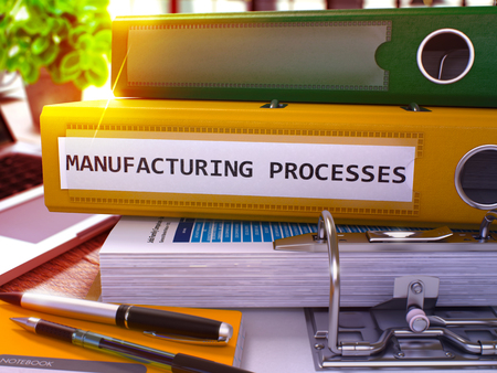 out of production: Yellow Ring Binder with Inscription Manufacturing Processes on Background of Working Table with Office Supplies and Laptop. Manufacturing Processes Business Concept on Blurred Background. 3D Render. Stock Photo