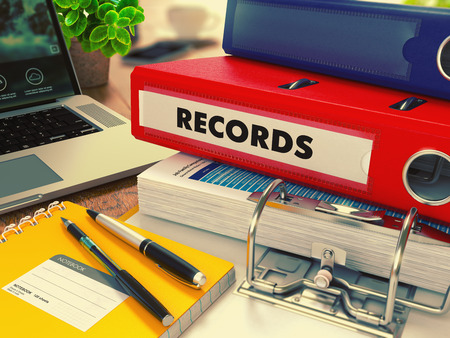 Red Office Folder with Inscription Records on Office Desktop with Office Supplies and Modern Laptop. Business Concept on Blurred Background. Toned Image. 3D Render.