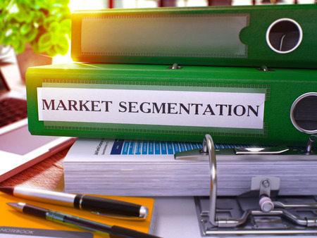 stationery needs: Market Segmentation - Green Office Folder on Background of Working Table with Stationery and Laptop. Market Segmentation Business Concept on Blurred Background. Market Segmentation Toned Image. 3D.