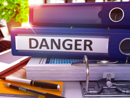 imminence: Blue Ring Binder with Inscription Danger on Background of Working Table with Office Supplies and Laptop. Danger - Toned Illustration. Danger Business Concept on Blurred Background. 3D Render.