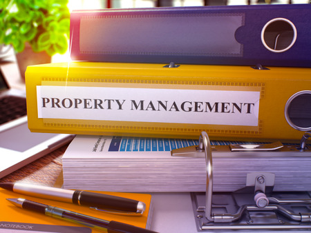 ownership and control: Yellow Ring Binder with Inscription Property Management on Background of Working Table with Office Supplies and Laptop. Property Management Business Concept on Blurred Background. 3D Render.