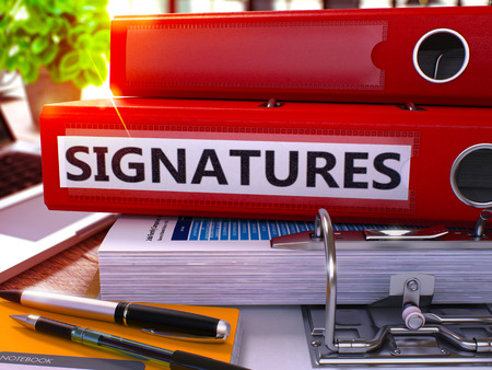 acknowledgment: Red Ring Binder with Inscription Signatures on Background of Working Table with Office Supplies and Laptop. Signatures Business Concept on Blurred Background. 3D Render. Stock Photo