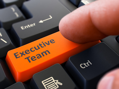 3d button: Executive Team Button. Male Finger Clicks on Orange Button on Black Keyboard. Closeup View. Blurred Background. 3D Render. Stock Photo