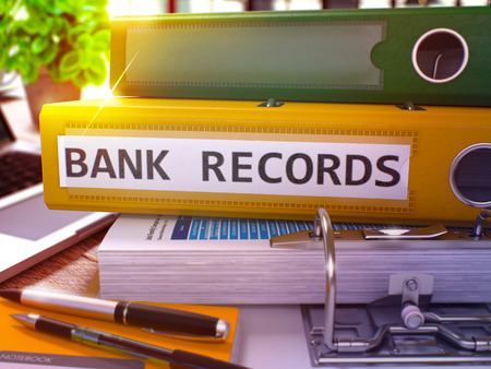 bank records: Yellow Ring Binder with Inscription Bank Records on Background of Working Table with Office Supplies and Laptop. Bank Records Business Concept on Blurred Background. 3D Render. Stock Photo