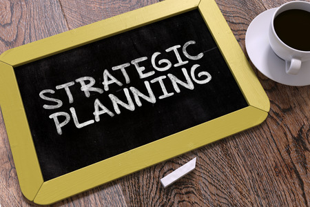 planificacion estrategica: Planificación Estratégica concepto dibujado mano en la pizarra amarilla en la mesa de madera. Conocimiento de los negocios. Vista superior. Render 3D.