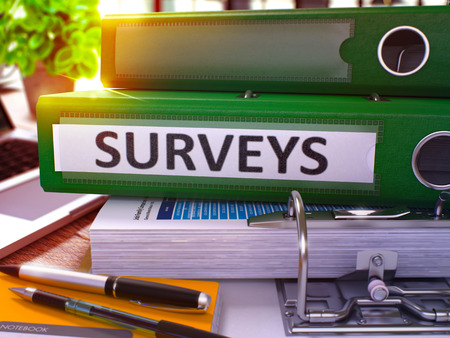 derivation: Surveys - Green Office Folder on Background of Working Table with Stationery and Laptop. Surveys Business Concept on Blurred Background. Surveys Toned Image. 3D. Stock Photo