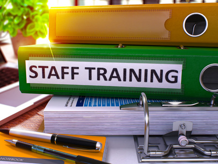 staff training: Staff Training - Green Office Folder on Background of Working Table with Stationery and Laptop. Staff Training Business Concept on Blurred Background. Staff Training Toned Image. 3D.