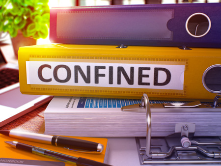 confined: Confined - Yellow Office Folder on Background of Working Table with Stationery and Laptop. Confined Business Concept on Blurred Background. Confined Toned Image. 3D Render. Stock Photo