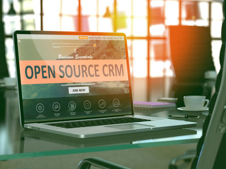 source: Modern Workplace with Laptop showing Landing Page with Open Source CRM - Customer Relationship Management - Concept. Toned Image with Selective Focus. 3D Render. Stock Photo