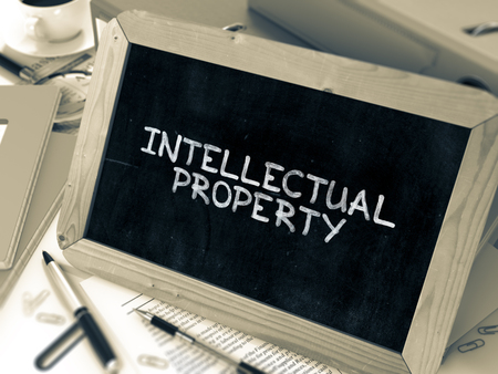 intellectual property: Intellectual Property Handwritten on Chalkboard. Composition with Small Chalkboard on Background of Working Table with Ring Binders, Office Supplies, Reports. Blurred, Toned Image. 3D Render.