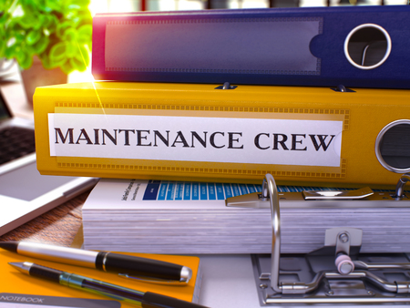 qualitatively: Yellow Ring Binder with Inscription Maintenance Crew on Background of Working Table with Office Supplies and Laptop. Maintenance Crew Business Concept on Blurred Background. 3D Render. Stock Photo