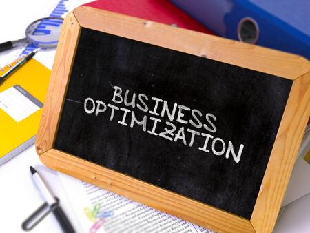 alteration: Business Optimization Handwritten on Chalkboard. Composition with Small Chalkboard on Background of Working Table with Ring Binders, Office Supplies, Reports. Blurred, Toned Image. 3D Render.