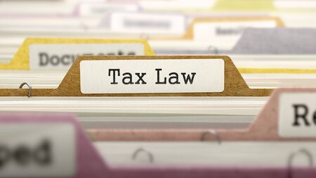 tax law: Folder in Colored Catalog Marked as Tax Law Closeup View. Selective Focus. 3D Render. Stock Photo