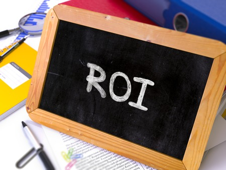 coefficient: Handwritten ROI -  Return on Investment - on a Chalkboard. Composition with Chalkboard and Ring Binders, Office Supplies, Reports on Blurred Background. Toned Image. 3D Render. Stock Photo