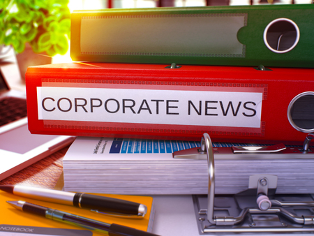 domestic policy: Red Ring Binder with Inscription Corporate News on Background of Working Table with Office Supplies and Laptop. Corporate News Business Concept on Blurred Background. 3D Render. Stock Photo