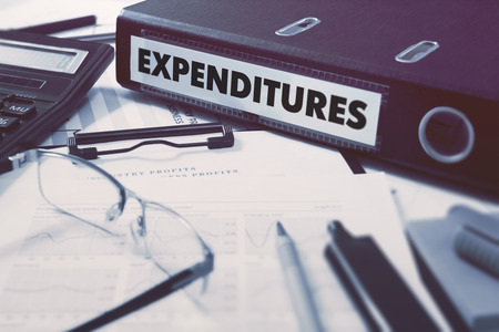 minimization: Ring Binder with inscription Expenditures on Background of Working Table with Office Supplies, Glasses, Reports. Toned Illustration. Business Concept on Blurred Background.