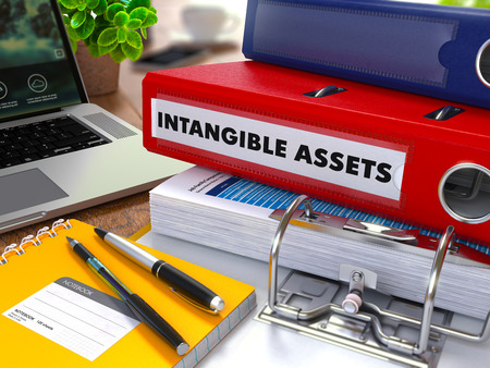 intangible: Red Ring Binder with Inscription Intangible Assets on Background of Working Table with Office Supplies, Laptop, Reports. Toned Illustration. Business Concept on Blurred Background. 3D Render.
