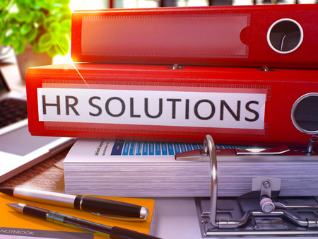 solution: Red Ring Binder with Inscription HR - Human Resource - Solutions on Background of Working Table with Office Supplies and Laptop. HR Solutions Business Concept on Blurred Background. 3D Render.