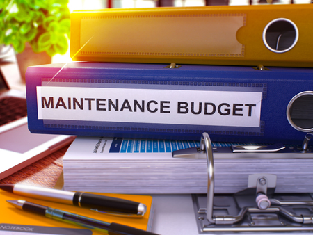 budget repair: Blue Office Folder with Inscription Maintenance Budget on Office Desktop with Office Supplies and Modern Laptop. Stock Photo