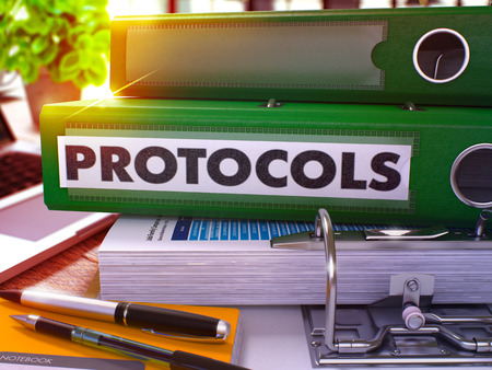 protocols: Protocols - Green Office Folder on Background of Working Table with Stationery and Laptop. Protocols Business Concept on Blurred Background. Protocols Toned Image. 3D. Stock Photo