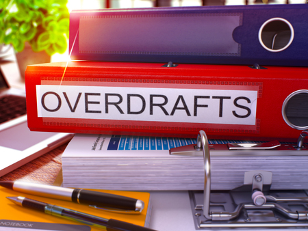 overdraft: Red Office Folder with Inscription Overdrafts on Office Desktop with Office Supplies and Modern Laptop. Overdrafts Business Concept on Blurred Background. Overdrafts - Toned Image. 3D.