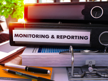 reporting: Black Office Folder with Inscription Monitoring and Reporting on Office Desktop with Office Supplies and Modern Laptop. Monitoring and Reporting Business Concept on Blurred Background. 3D Render. Stock Photo
