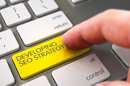 teclado: Desarrollo de la estrategia de SEO - Concepto del teclado de ordenador. El desarrollo del concepto de SEO Estrategia. El desarrollo de la mano Empujar amarillo botón del teclado SEO Estrategia metálico. Render 3D.