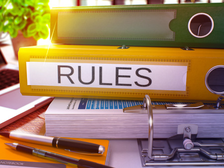 rectification: Rules - Yellow Office Folder on Background of Working Table with Stationery and Laptop. Rules Business Concept on Blurred Background. Rules Toned Image. 3D.