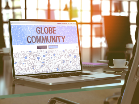 mercifulness: Globe Community Concept. Closeup Landing Page on Laptop Screen in Doodle Design Style. On Background of Comfortable Working Place in Modern Office. Blurred, Toned Image. 3D Render. Stock Photo