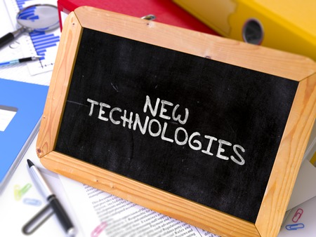 new technologies: New Technologies Handwritten by White Chalk on a Blackboard. Composition with Small Chalkboard on Background of Working Table with Office Folders, Stationery, Reports. Blurred, Toned Image. 3D Render.
