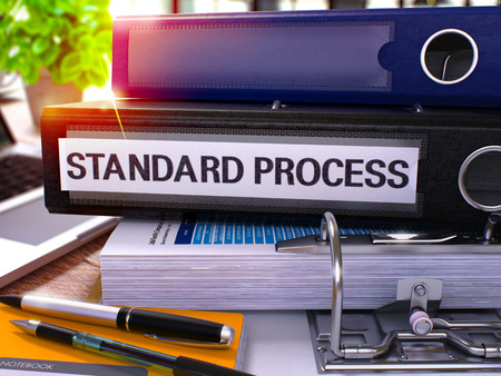norm: Standard Process - Black Office Folder on Background of Working Table with Stationery and Laptop. Standard Process Business Concept on Blurred Background. Standard Process Toned Image. 3D. Stock Photo