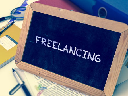 freelancing: Freelancing Handwritten by White Chalk on a Blackboard. Composition with Small Chalkboard on Background of Working Table with Office Folders, Stationery, Reports. Blurred, Toned Image. 3D Render.