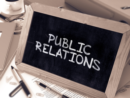 relaciones publicas: Public Relations Handwritten by White Chalk on a Blackboard. Composition with Small Chalkboard on Background of Working Table with Office Folders, Stationery, Reports. Blurred, Toned Image. 3D Render.