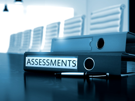 assessments: Assessments. Concept on Blurred Background. Binder with Inscription Assessments on Working Wooden Desktop. Toned Image. 3D Rendering.