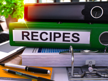 Recipes - Green Ring Binder on Office Desktop with Office Supplies and Modern Laptop. Recipes Business Concept on Blurred Background. Recipes - Toned Illustration. 3D Render. Stock Photo