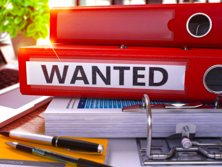 remuneraciones: Red Ring Binder with Inscription Wanted on Background of Working Table with Office Supplies and Laptop. Wanted - Toned Illustration. Wanted Business Concept on Blurred Background. 3D Render.