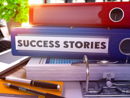 Success Stories - Blue Office Folder on Background of Working Table with Stationery and Laptop. Success Stories Business Concept on Blurred Background. Success Stories Toned Image. 3D.
