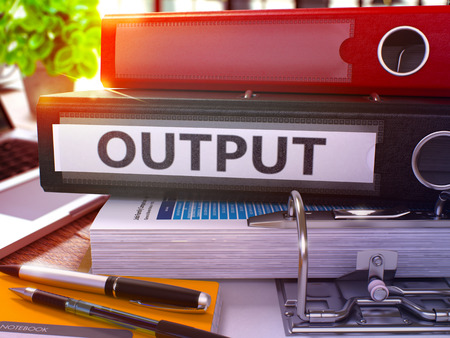output: Output - Black Office Folder on Background of Working Table with Stationery and Laptop. Output Business Concept on Blurred Background. Output Toned Image. 3D. Stock Photo