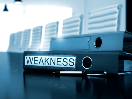 weakness: Weakness - Ring Binder on Desktop. Office Folder with Inscription Weakness on Black Wooden Desk. 3D. Stock Photo