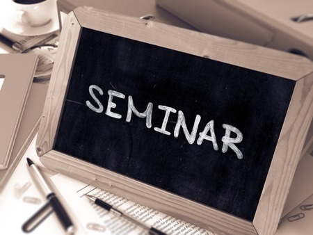 learning new skills: Seminar Handwritten by White Chalk on a Blackboard. Composition with Small Chalkboard on Background of Working Table with Office Folders, Stationery, Reports. Blurred, Toned Image. 3D Render. Stock Photo
