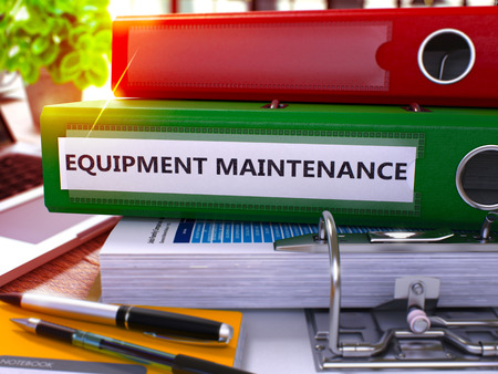 prophylactic: Green Ring Binder with Inscription Equipment Maintenance on Background of Working Table with Office Supplies and Laptop. Equipment Maintenance Business Concept on Blurred Background. 3D Render.