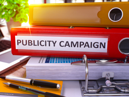 publicity: Publicity Campaign - Red Office Folder on Background of Working Table with Stationery and Laptop. Publicity Campaign Business Concept on Blurred Background. Publicity Campaign Toned Image. 3D.