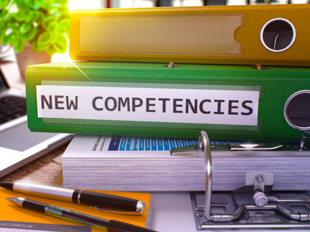 competencies: Green Ring Binder with Inscription New Competencies on Background of Working Table with Office Supplies and Laptop. New Competencies Business Concept on Blurred Background. 3D Render.